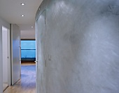 Gray curved wall in a hallway with open door and view of a window