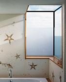Three-dimensional corner window and starfish motif above bathtub