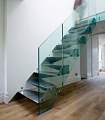 Metal, cubist designer stairs with glass balustrade in purist foyer