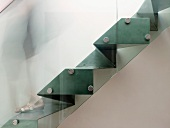 Side view of sculptural steel staircase with glass balustrade