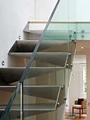 Detail of made-to-measure metal staircase with glass balustrade and view through open living room door