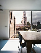 Rustic dining table in front of open sliding terrace door and view of church