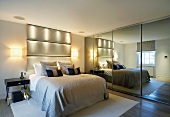 Double bed with upholstered head in modern bedroom next to mirrored sliding doors
