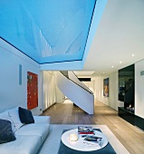 Modern, open-plan living space with curved stairs and sofa under glass panel in ceiling