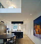 Dining area in front of designer kitchen counter and view of gallery through ceiling cut-out