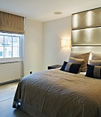 Double bed with ceiling-height upholstered head in modern bedroom