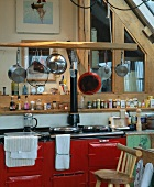 Vintage kitchen counter with red lacquered cabinets and hanging pots and pans