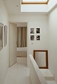 Stairway in a white hallway with open door to the bedroom