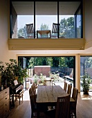Rustic dining table with chairs in front of an open patio door and view of a glass covered cut-out with a loggia upstairs