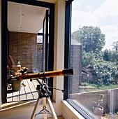 Telescope on a tripod in front of a large bank of windows