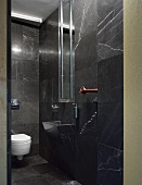 Designer bath with black marble tiles on the wall and floor and integrated vanity