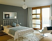 Bedroom with double bed and modern, white bed stead in front of a gray wall