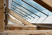 Modern skylight above old, rustic wooden construction