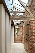 Renovated hallway with old brick facade and rustic wooden construction below a skylight