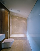 Minimalist bathroom with sand-colored floor and wall tiles and glass shower enclosure