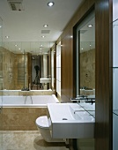 Modern vanity with ceiling high wood frames and bathtub in front of a mirrored wall