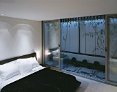 Modern bedroom with a double bed in front of an open, beautifully designed terrace at dusk