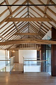Gallery with a bridge in a renovated barn and view of rustic wood timbers