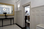 Lobby with white wood paneling on the wall and open living room door across from an antique console table with mirror