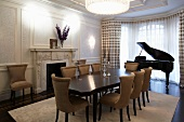 Dining table with upholstered chairs in Art Deco style in front of a grand piano in the bay window