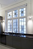 Designer kitchen counter with brown cabinets and glossy countertop in front of leaded glass windows
