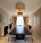 Long dining table with dark surface and upholstered chairs under a hanging lamp with gold shade
