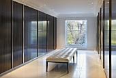 Klassizistische Sitzbank mit weißem Lederpolster vor Holzschiebetüren und glänzender Oberfläche in eleganter Ankleide