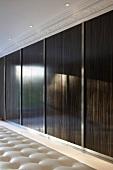Holzschiebetüren mit glänzender Oberfläche und Deckenstrahler vor Stuckfries in eleganter Ankleide