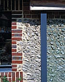 Detail of a natural stone wall with a brick surround