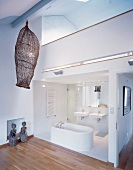 Open bath with a white freestanding bathtub under a gallery