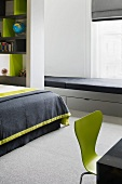 Light gray lacquered window seat upholstered in black and drawers in a modern bedroom with green retro chair