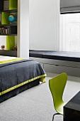 Hellgrau lackierte Sitzbank mit schwarzen Polstern und Schubladen im modernem Schlafraum mit grünem Retrostuhl