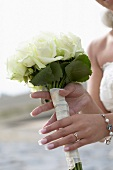 A bride holding a small bunch of white roses