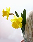 Blond lady holding two daffodils