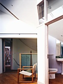 Wood frame chair and sailcloth in front of a wall with a view through an open bathroom door of the toilet
