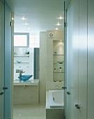 weiße Einbauschränke vor offener Badtür mit Blick auf Badewanne und Waschtisch