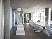 White stair landing in front of stairs in an open living room with shell chairs (in Bauhaus style) in front of a dining table