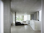 Open living room in concrete with enclosed white banister around a stairway