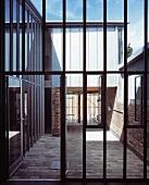 Steel and glass facade with open patio door and view of a courtyard