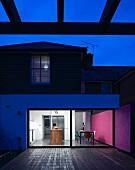 Zeitgenössisches Wohnhaus mit beleuchtetem Wohnraum in Abendstimmung