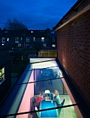 Evening mood - view through a skylight of a dining table with a family playing chess