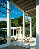 Contemporary villa with veranda and white columns beside a free standing extension