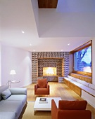 Schlichter Wohnraum mit farbigen Polstersesseln und Ziegelwand mit eingebautem Kamin