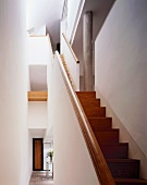 White stairwell with airspace and multi-level wood stairs
