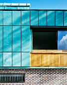 Turquoise colored panels on the wall of a house above a brick facade