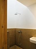 Minimalistischer Duschbereich mit halbhoher Steinverkleidung