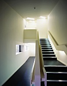 Minimalist stairway with black floor covering in the passage way and on the steps