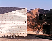 Bike racks in front of a house with a wood clad roof and wall