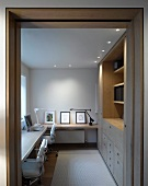 View through a door into a work room with counter and recessed ceiling spotlights above a built-in cabinet