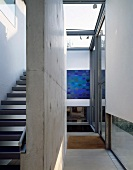 Modern, open stairway with concrete dividing wall